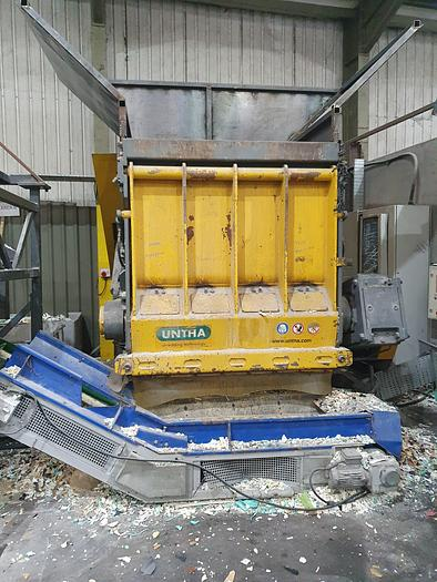 Used UNTHA Plastic shredder with bag stand magnet and out feed conveyor.